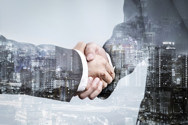 Double exposure of business partnership handshake and modern cit